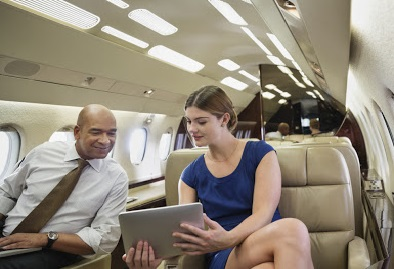 Businesswoman showing digital tablet to colleague in airplane